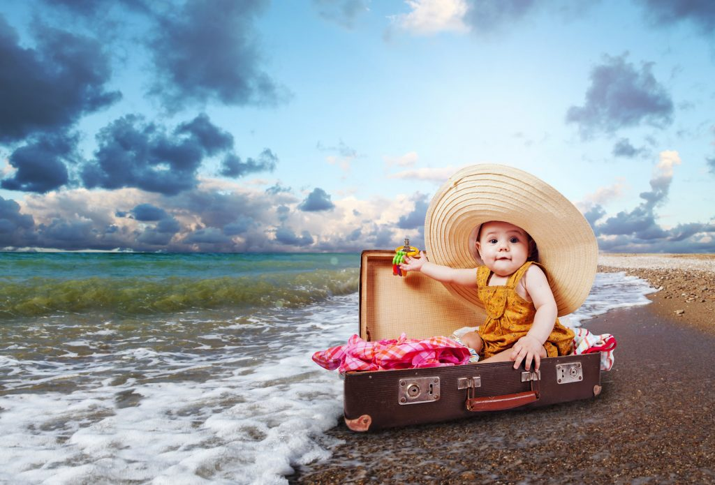 Little baby girl in big sun hat sitting into retro suitcase at the sea coast